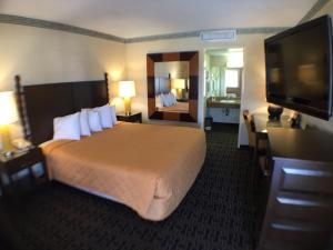 A bed or beds in a room at Days Inn by Wyndham Fresno Central