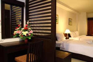 A bed or beds in a room at The White Pearl Hotel