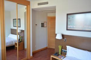 A bed or beds in a room at Hotel Palacio Congresos