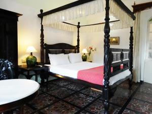 سرير أو أسرّة في غرفة في WelcomHeritage Panjim Inn