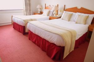 A bed or beds in a room at The Rhu Glenn Hotel