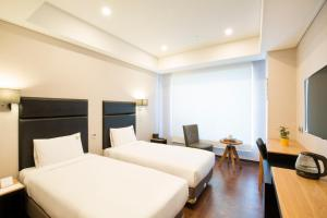 A bed or beds in a room at Benikea Hotel Haeundae