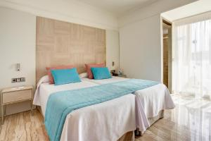 A bed or beds in a room at Grupotel Orient
