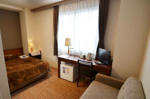 A bed or beds in a room at Kashihara Oak Hotel