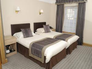 A bed or beds in a room at OYO Burnett Arms Hotel