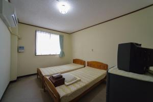 A bed or beds in a room at Sudomarikan