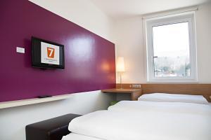 A bed or beds in a room at 7 Days Premium Hotel Salzburg-Urstein