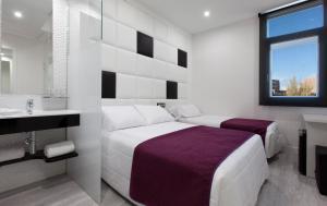 A bed or beds in a room at Hotel Avenida de España