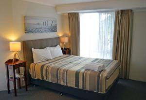 A bed or beds in a room at Arkana Motor Inn & Terrace Apartments