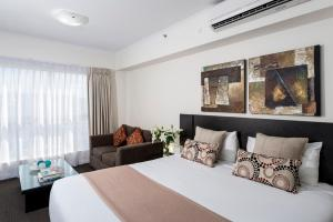A bed or beds in a room at Oaks Ipswich Aspire Suites