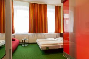A bed or beds in a room at Pension Stadthalle