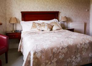 A bed or beds in a room at Lasswade Country House & Restaurant