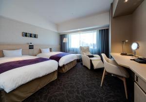A bed or beds in a room at Daiwa Roynet Hotel Matsuyama