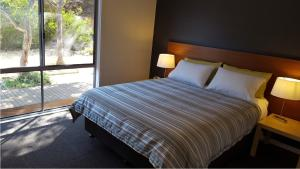 A bed or beds in a room at Coorong Waterfront Retreat