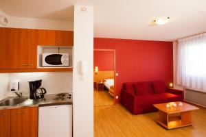 A kitchen or kitchenette at Séjours & Affaires Genève Saint Genis