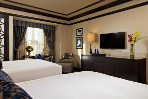 A bed or beds in a room at Saratoga Casino Hotel
