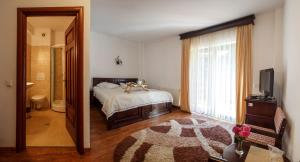 A bed or beds in a room at Pension Perla Bucovinei