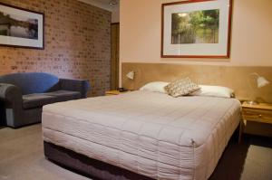 A bed or beds in a room at Baybrook Motor Inn