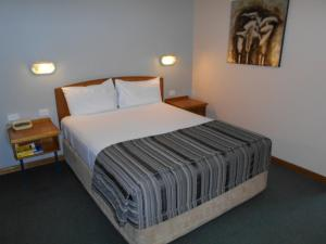 A bed or beds in a room at Cannon Park Motel