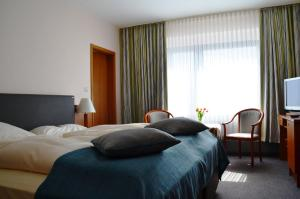 A bed or beds in a room at Hotel Exquisit