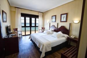 A bed or beds in a room at Hotel Ribadesella Playa