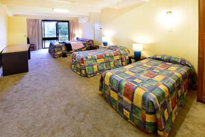 A bed or beds in a room at Armidale Motel