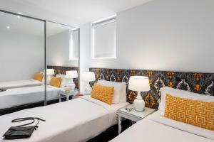 A bed or beds in a room at Oaks Melbourne South Yarra Suites