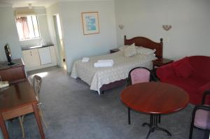 A bed or beds in a room at Elite Motor Inn