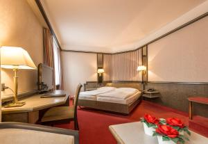 A bed or beds in a room at Hotel Monopol Luzern