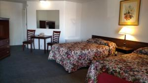 A bed or beds in a room at Essex House Motel