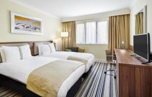 A bed or beds in a room at Holiday Inn Cardiff North M4 Jct 32