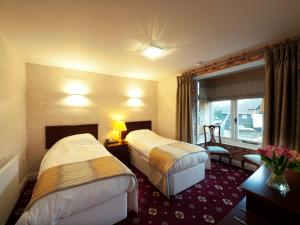 A bed or beds in a room at Brambletye Hotel