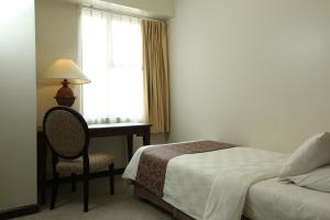 A bed or beds in a room at Aryaduta Suite Semanggi