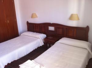 A bed or beds in a room at Hostal Rios