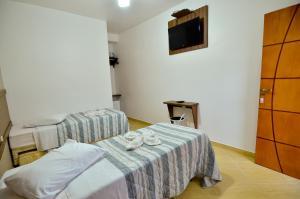 Cama ou camas em um quarto em Hotel Pousada da Capital da Fe