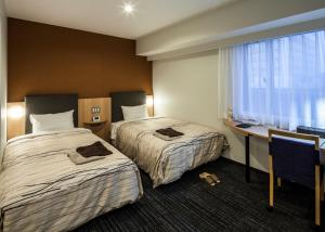 A bed or beds in a room at Fukui Manten Hotel Ekimae