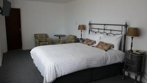 A bed or beds in a room at Halfway House Hotel