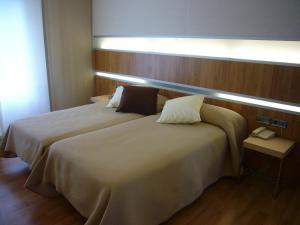 A bed or beds in a room at Hotel El Mesón