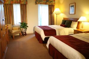 A bed or beds in a room at Rocklin Park Hotel