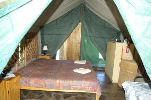 A bed or beds in a room at Etusis Lodge
