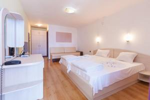 A bed or beds in a room at Akladi Family Hotel