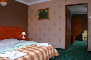 A bed or beds in a room at Hotel Zbyszko