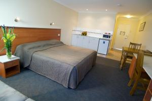 A bed or beds in a room at Scone Motor Inn & Apartments