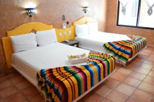A bed or beds in a room at Hacienda Maria Bonita Hotel