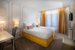 A bed or beds in a room at Hôtel Paris Vaugirard