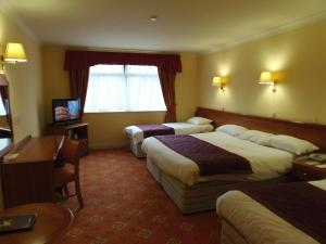 A bed or beds in a room at Lakeside Continental Hotel