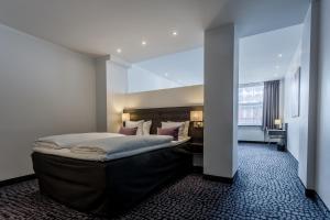 Säng eller sängar i ett rum på ProfilHotels Mercur Hotel