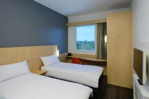 A bed or beds in a room at Ibis Manaus Aeroporto