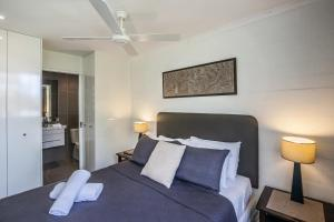 A bed or beds in a room at Noosa Harbour Resort