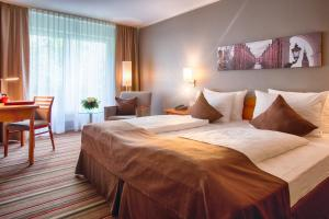 A bed or beds in a room at Leonardo Hotel Hamburg Airport